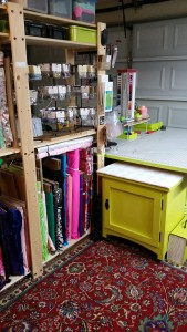 View of the southwest corner. Lots of rhinestones on racks, and a partial view of the dining room table - turned - cutting table. I didn't get a good picture of it, but it holds a giant white cutting mat on one side, and various cutting table supplies on the other.  There's a better photo of the cutting table in a previous post.